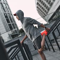 Relaxing exercise. Full length of young man in sports clothing warming up while exercising outdoors