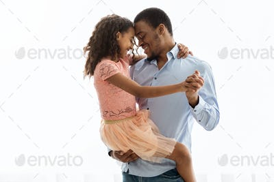 Cute black father and daughter dancing over white