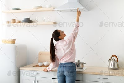 Smiling woman select mode on cooking hood in kitchen
