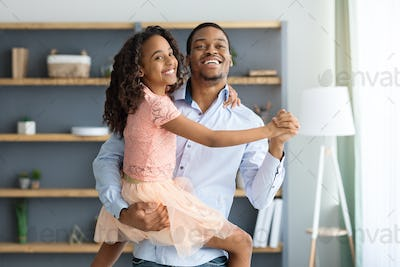 Cheerful little black girl dancing with her dad