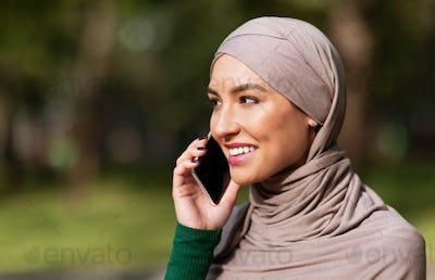 Happy Muslim Woman Talking On Phone Calling Friend Standing Outdoors