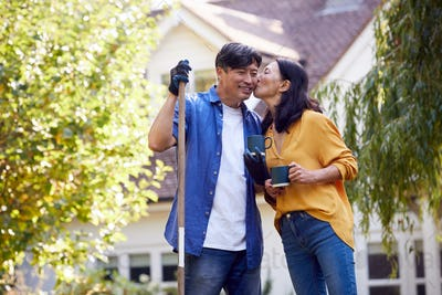 Loving Mature Asian Couple Taking A Break With Hot Drinks Whilst Tidying Garden With Rake
