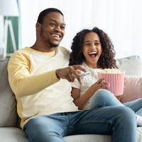 Joyful black family father and daughter watching movie together
