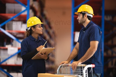 Group of warehouse workers logistic team  wearing hardhats working in aisle between tall racks