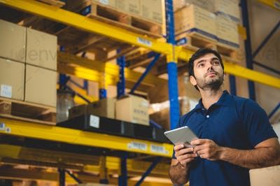 Male warehouse worker working for check and analyze newly arrived goods for further placement
