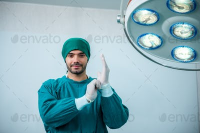 Portrait of male surgeon doctor doing surgery in hospital operating theater
