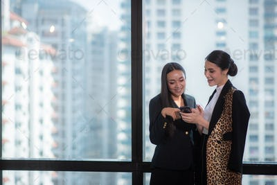 A couple business woman colleague enjoy together by taking a mobile phone at the office