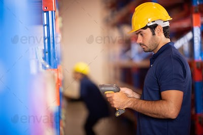 warehouse worker using bar code scanner to analyze newly arrived goods for further placement