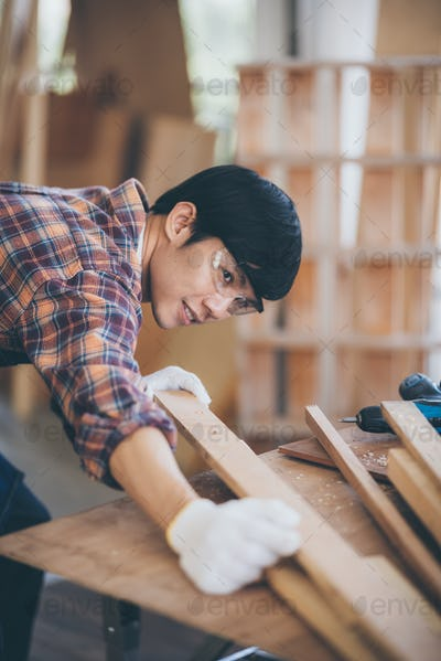 carpenter is selecting wood for making furniture, wooden handcraft working at home