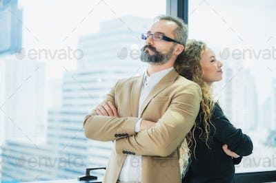 Two business colleagues partner are standing and talking together at the office work space