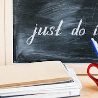 Lettering of phrase JUST DO IT on black chalkboard on a background of notepads and diary and a red