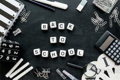 """Black and white school supplies and words """"Back to school"""" from white cubes on blackboard"""
