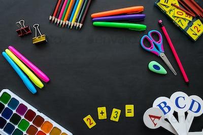 School supplies mockup on blackboard background with copyspace. Bright multicolored, pencils, pens