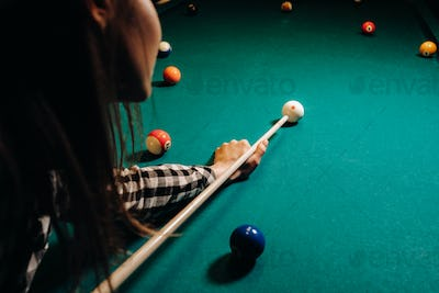 A girl in a hat in a billiard club with a cue in her hands hits a ball.Playing pool