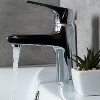Panoramic shot of flowing water from sink to washbasin with plant in restroom