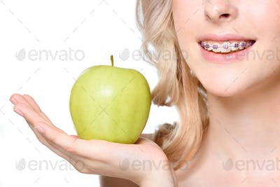 Cropped shot of a young woman with braces holding a fresh green apple on her hand.