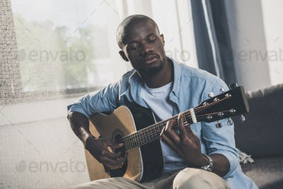 African american man playing acoustic guitar at home