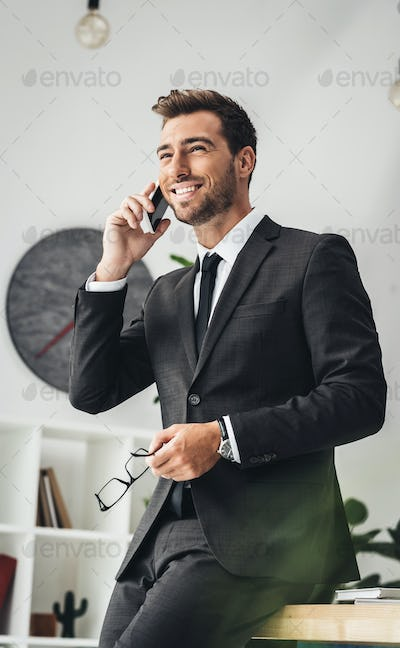 young businessman talking by phone while leaning back on worktable