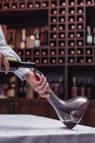 Cropped view sommelier pouring red wine from bottle into decanter at table in cellar