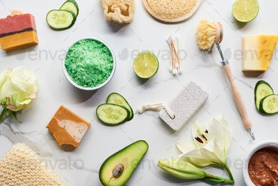 top view of natural beauty products and gadgets and soap pieces near fresh flowers, vegetables and