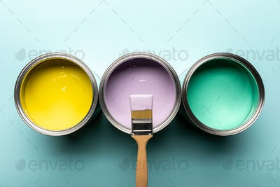 top view of three tins with paints and brush on blue surface