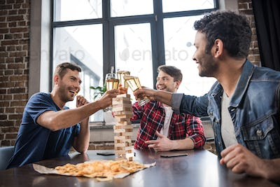 diverse group of young people playing jenga game and drinking beer