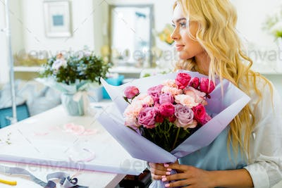 beautiful female florist holding bouquet with roses and carnations in flower shop and looking away