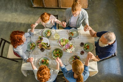overhead view of family holding hands and praying while having dinner together