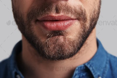 Real man.  Close up of young unshaved man standing against grey background