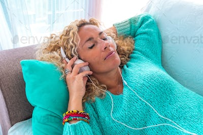 close up of beautiful curly woman on the sofa listening music with headphones relaxing