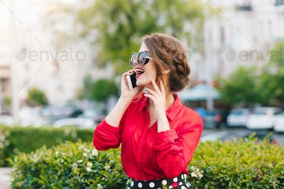 Horizontal portrait of pretty girl in sunglasses walking in park. She wears red blouse and nice