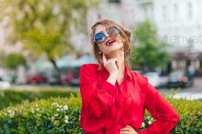 Close-up portrait of gorgeous girl in sunglasses posing to the camera in park. She wears red blouse
