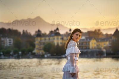 A bride in a white wedding dress in the old town of Austria at sunset
