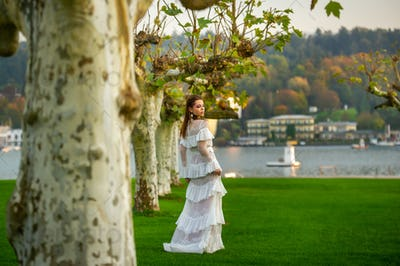 A bride in a white wedding dress in a park in an Austrian town with large trees at sunset