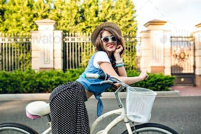 Cute girl with long curly hair in hat posing on bike on road. She wears long skirt, jerkin, blue sun