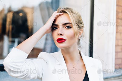 Closeup portrait attractive woman with red lips on street . She wears white jacket, touching hair, l