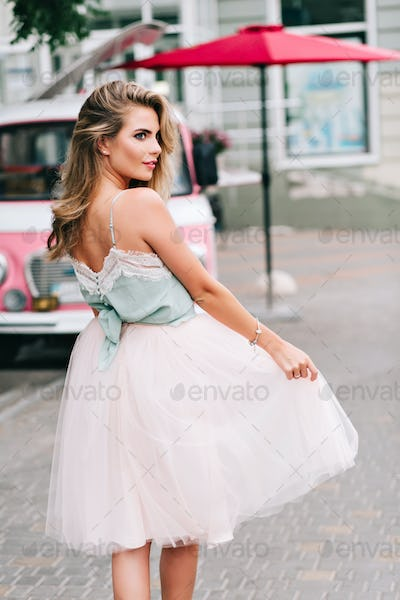 View from back attractive girl with long blonde hair walking on street. She wears light tulle skirt,