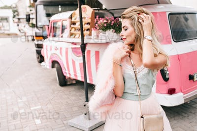 Fashion model with a long blonde hair on retro car background. She holds pink fur stole on shoulder,