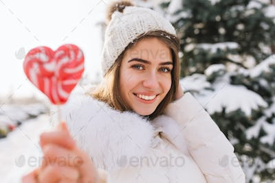 Closeup portrait amazing joyful smiling girl in sunny winter morning with pink lollypop on street. A