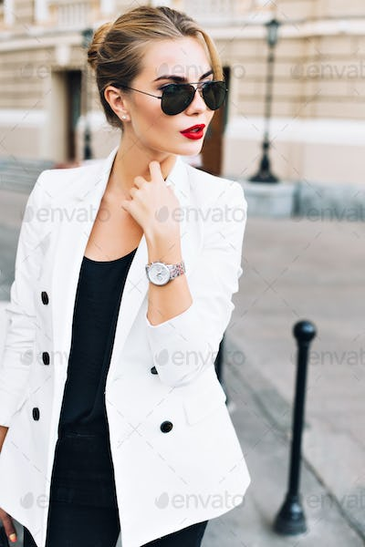 Portrait pretty woman in sunglasses with red lips on street . She wears white jacket, looking to sid