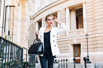 Portrait pretty woman in white jacket walking on street . She has red lips, smiling to side