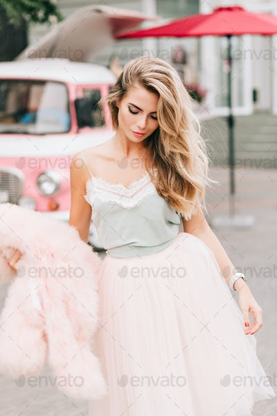 Fashion model in tulle skirt on retro car background. She has long blonde hair, holds pink fur coat