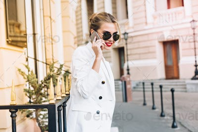 Portrait pretty woman in white jacket and black sunglasses on street. She speaking on phone and smil