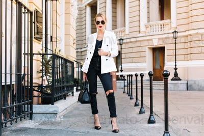 Fashion blonde woman in sunglasses is walking on street on high heels. She wears white jacket and bl