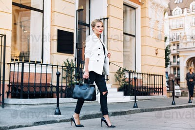 Fashion blonde woman on heels in white jacket is walking on street. She smiling to side