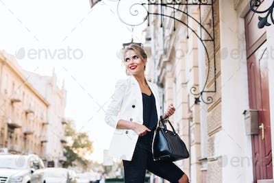 Attractive model in white jacket on street in city. She has red lips, smiling to side