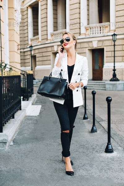 Fashion model in sunglasses is walking on street on heels. She speaking on phone and smiling to side