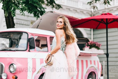 View from back fashion model in tulle skirt on retro coffee car background. She has long blonde hair