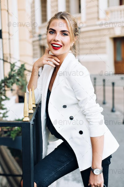 Portrait pretty woman leaning on fence on street. She wears white jacket, has red lips, smiling to c