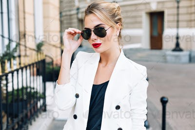Portrait fashion woman in sunglasses with red lips on street . She wears white jacket, looking to ca